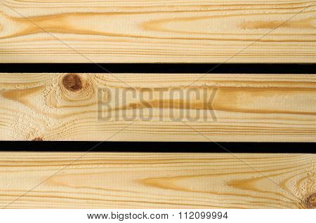 Background of raw wooden pine planks or boards showing woodgrain texture with gaps