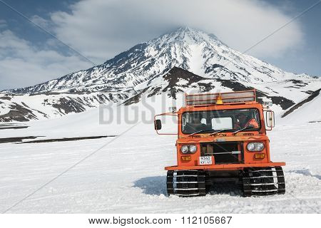 Snowcat On Snowy Slopes Of Mountain On Background Volcano