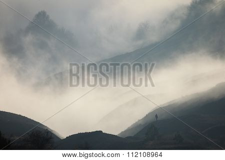 Silhouette Of A Man In A Fog Against The Backdrop Of Mountain Slopes