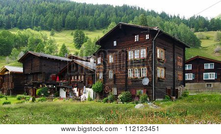 The ancient traditional chalet and Church along the Furkastrasse. Floral decoration on the facades i