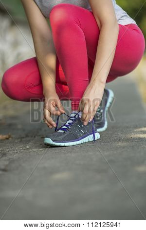 Young sports girl tying shoelaces on sneakers cross-country.