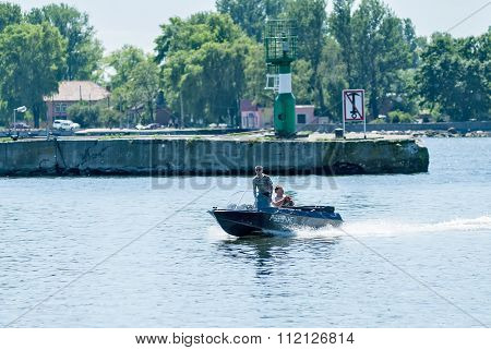 Men go on the boat is Baltiysk. Russia