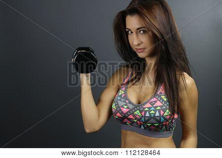 Beautiful brunette holding a dumbbell