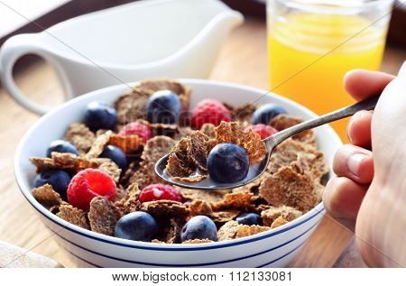 Hand holding a spoonful of bran flakes with blueberry, orange juice and milk jug in the background