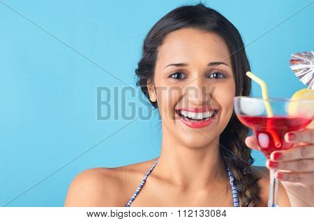 Beautiful woman wearing bikini holding red mixed drink cocktail with umbrella, isolated on bright blue background