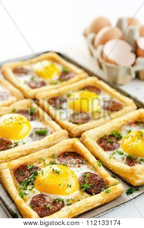 Egg and sausage (chorizo) puff pastry tarts baked to golden perfection, with a carton of eggs in the background