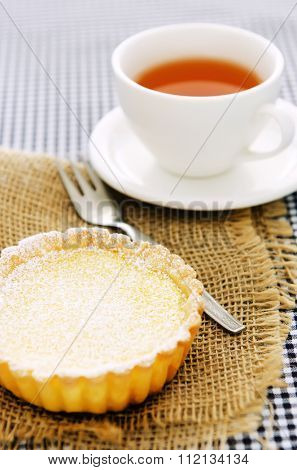Yummy looking yellow lemon tart served with tea, with hessian and checkered background