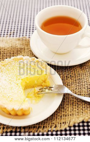 Half eaten yellow lemon tart served with tea, with hessian and checkered background