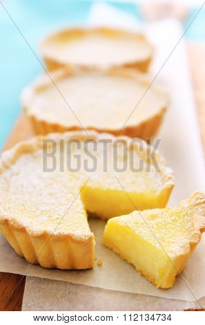 Lemon flavoured tarts on a serving platter, with a slice cut from one of the tarts