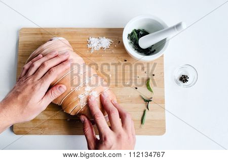 Chef hands rubbing salt spices seasoning into a piece of fresh raw meat, preparing a pork roast