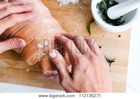 Close up of chef hands rubbing salt spices seasoning into raw meat, pestle and mortar with herbs