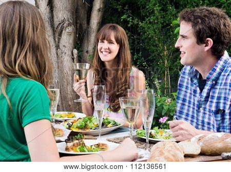 Group of friends talking and enjoying themselves at a outdoor garden party with food and wine drinks