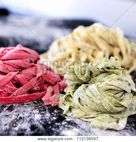 Close up of raw home hand made fresh pasta with variety of flavours, beetroot, herb, spinach