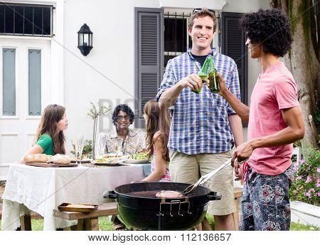 Two men having beers by the barbeque at a party, with meat on the smoking grill