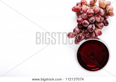 Glass of red wine with bunch of grapes, overhead on white background, minimalist arrangement