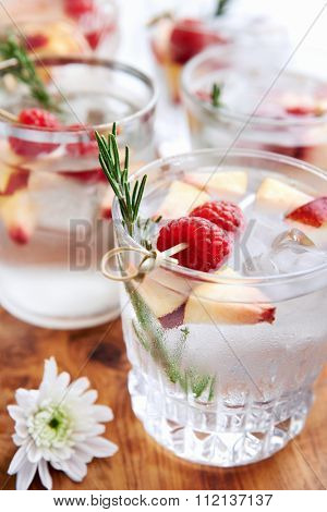 Cool fruity cocktails/soda water served on a wooden tray decorated with flowers, raspberries, sliced nectarine and garnish