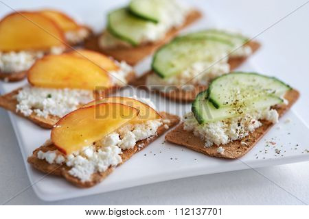 Fresh ricotta cottage cheese healthy snack starter platter with sliced peach nectarine and cucumber, perfect party canapes