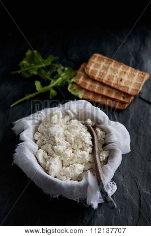 Homemade ricotta cheese made from milk, draining in muslin cheese cloth on dark background