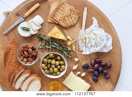 Gourmet selection of cheeses, cheddar fresh ricotta gouda brie goat cheese, with nuts olives grapes crackers and bread, served on a large wooden board