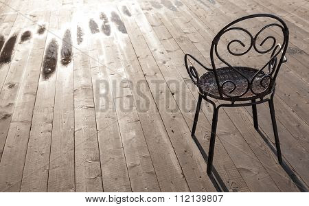 Old Black Wrought-iron Chair Standing On Wooden Floor