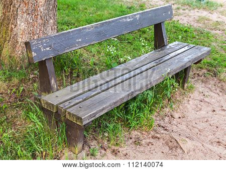 Old Wooden Bench On Roadside Grass In Park