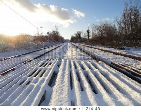 Snow Covered Railway Crossing And Tracks