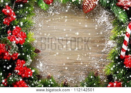 Christmas fir tree branches with rowan and toys on wooden table