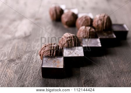 Tasty chocolate candies on wooden background. V-shaped