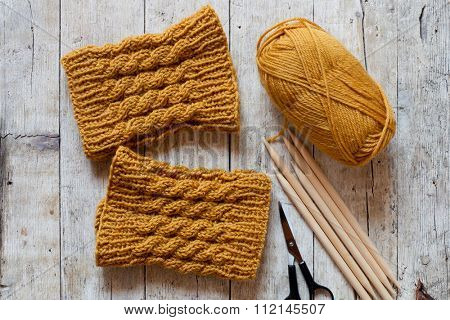 wool yellow legwarmers, scissors, knitting needles and yarn on wooden background