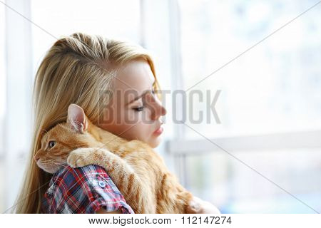 Young woman with red cat in hands looking at window, close up