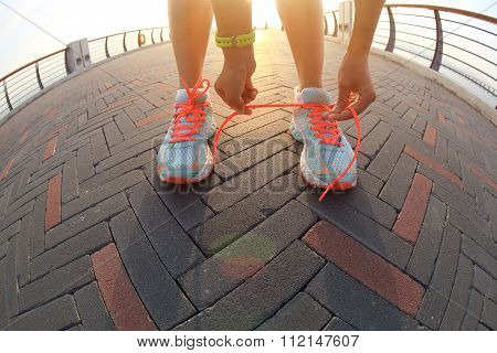 one young woman runner tying shoelace outdoor