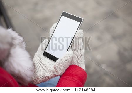 Traveling woman with mobile phone, cold weather