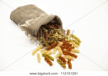Beautiful Italian pasta Fusilli from durum wheat  in a linen sack, closeup on a white background.