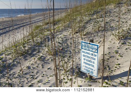 Sign Warns Of Vegetation Destruction On Dunes By The Sea