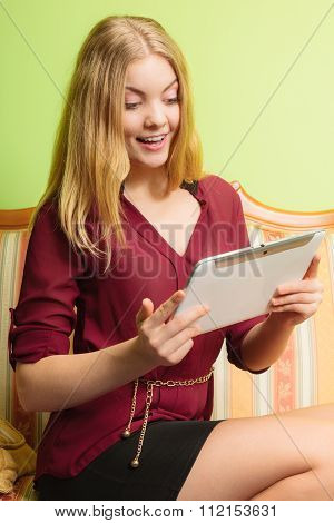 Fashion Woman Sitting On Sofa With Pc Tablet.