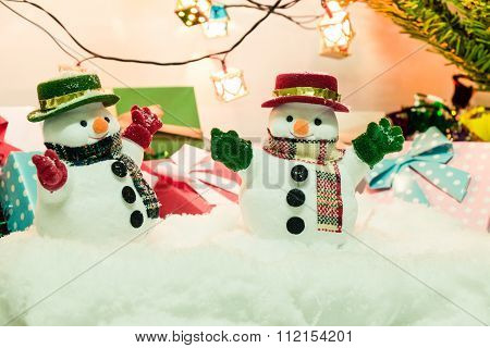 Snowman Stand In Pile Of Snow At Silent Night, Ornament And A Light Bulb Decorate For  Merry Christm