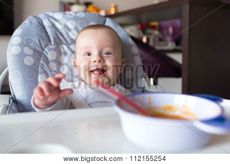 Baby boy sitting on the high chair for lunch