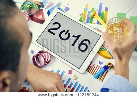 a young caucasian businessman celebrates the new year in his office with a glass with liquor in his hand and the number 2016 in the screen of a tablet, and some party horns, streamers and confetti
