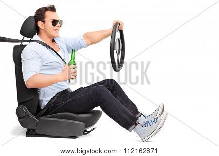 Careless young man driving and holding a bottle of beer isolated on white background