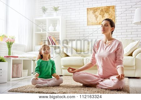 beautiful girl is engaged in yoga with her daughter