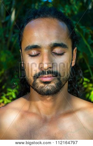 Close up of bearded young man with no shirt meditating against greenery background.