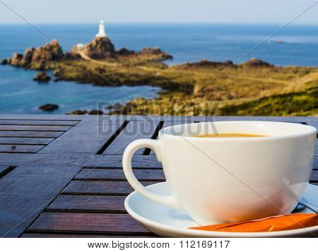 Big white cup on a table and seacoast as a background