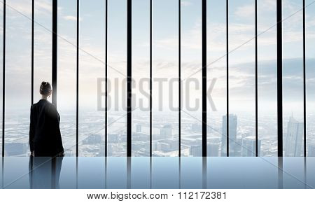 Back view of businesswoman looking in office window