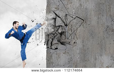 Young determined karate man breaking with leg concrete wall