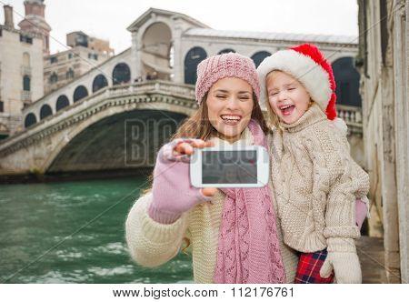 Happy Mother And Child In Santa Hat Taking Selfie In Venice