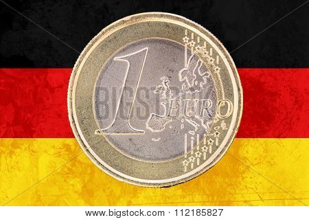 One Euro Coin On The Flag Of Germany As Background
