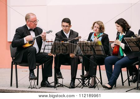 People from city string band Orchestra playing music on street i