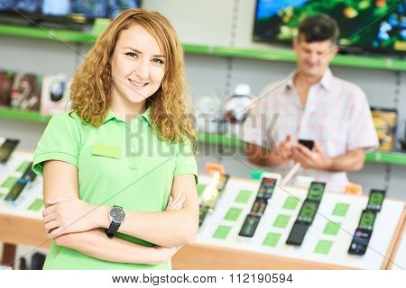 Portrait of young happy female seller assistant  in electronics retail store