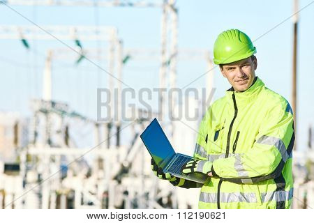 Engineering supervision. Portrait of male service engineer in high visibility reflecting clothing and hard hat working on notebook computer at heat electropower station