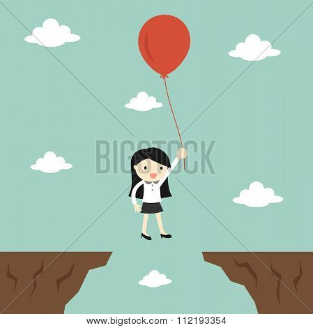 Business concept, business woman flies across gap to another cliff by using balloon.